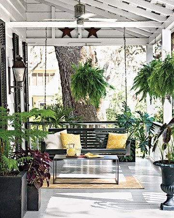 love the bold porch swing... adding a coffee table really makes this look like an entertaining space