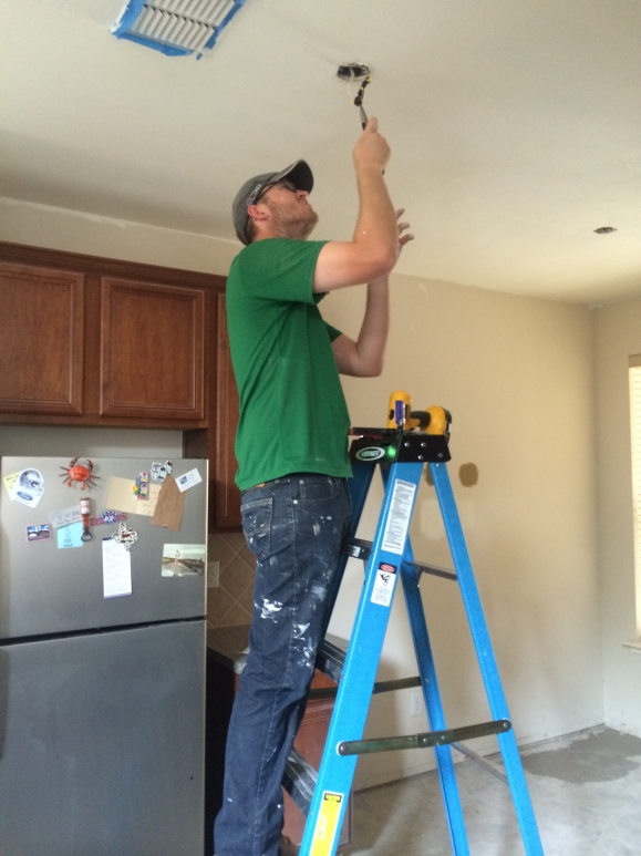 And finally a great shot of a freshly painted ceiling and my man installing one of many new light fixtures in our home! A huge THANK YOU to David's mom for helping him paint and making sure he was safe... also for getting me this picture! :)